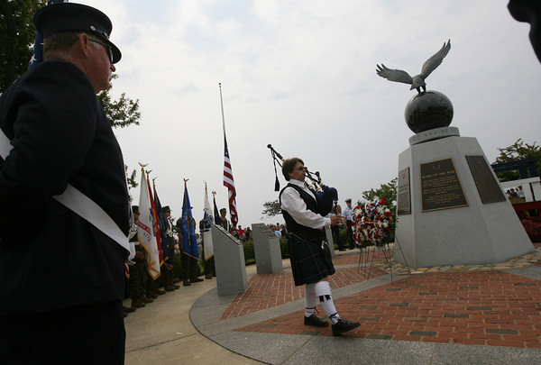 "Cindy Carrancho plays ""Amazing Grace"" as she circles the World War II Memorial in McKinnon Triangle during Gloucester's Memorial Day ceremony yesterday morning. Photo by Kate Glass/Gloucester Daily Times"