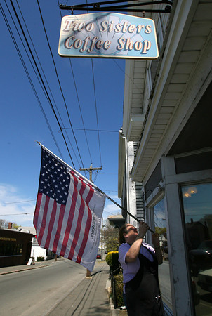 Patty Philbrick of Two Sisters Coffee Shop in Gloucester, untwists her Flag of Honor outside the restaurant yesterday morning. The flag contains the names of those killed in the terrorist attacks of September 11th and Philbrick put it up after hearing the news that Osama bin Laden had been killed. Photo by Kate Glass/Gloucester Daily Times
