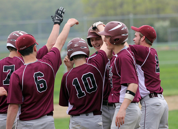 Essex: Members of the Rockport baseball team greet Derek MacDowell at home plate after he hit a home run against Manchester Essex yesterday. Photo by Kate Glass/Gloucester Daily Times