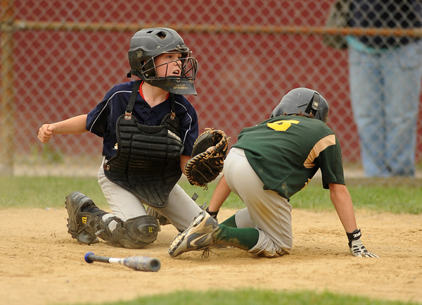 Gloucester:Twins catcher E.J Field looks to the plate umpire as Athletic's Geoffrey Lattanzi touches home plate after being knocked in by a Cobby Mitchell's base hit, tying the game 7-7 in the 6th inning Saturday afternoon at Boudreau Field. Desi Smith Gloucester Daily Times.