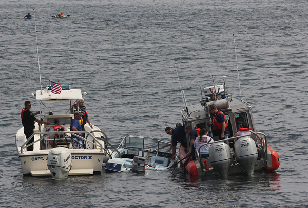 The Gloucester Harbormaster, Gloucester Police, and the U.S. Coast Guard tow a boat that began taking on water near the Blynman Bridge yesterday afternoon. The boaters were rescued from the water. Photo by Kate Glass/Gloucester Daily Times