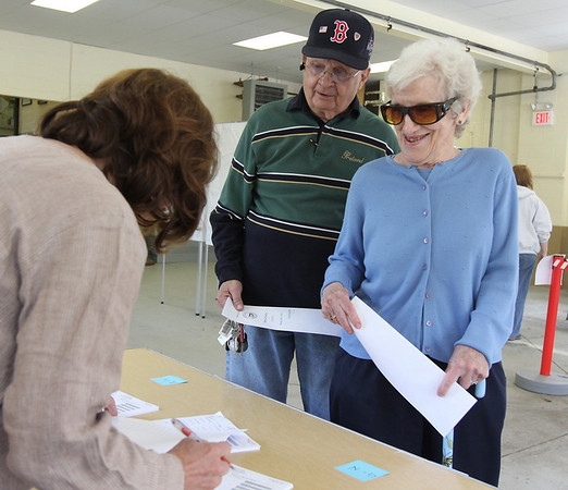 Sandy Ginn checks off the names of Edwin and Margaret Richter as they vote at the Essex Fire Station in the town election yesterday. Photo by Kate Glass/Gloucester Daily Times