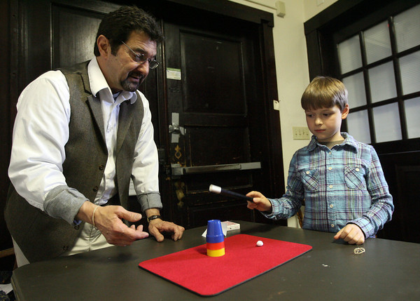 Essex: Noah Stevens assists Master Magician Richard during his magic class at the TOHP Burnham Library on Monday afternoon. Kids learned a trick with a rubber band, paper clips, and cups and balls. There will be three more classes on Mondays at 5 p.m. Photo by Kate Glass/Gloucester Daily Times