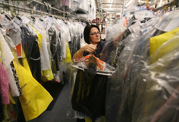 Maria Silva hangs clothes that will be going out for delivery from Nor'east Cleaners. The business was one of the first in the country to convert to an environmentally safe process for their dry cleaning operations. Photo by Kate Glass/Gloucester Daily Times