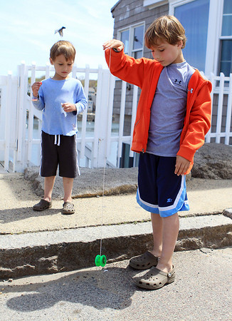 DAVID LE/Gloucester Times. Bennett Newman, 9, right, plays with his yo-yo while his little brother Hudson, 4, looks on in amusement. 5/13/11.