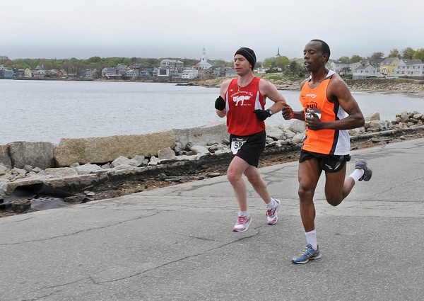 Gloucester: Beverly's John Ayers left, keeps place with David Ndungu in the Twin Lights Half Marathon as they pass Front Beach in Rockport Sunday morning. Ndungu beat Ayers to the finish at Good Harbor Beach where it started with a time of 1:15:47 Desi Smith/Gloucester Daily Times.