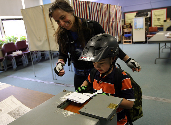 Rockport: Michelle Lizotte watches as her son, Oliver Dunton, 6, places her ballot in the box during the town election yesterday. Photo by Kate Glass/Gloucester Daily Times