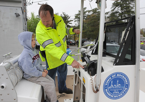 Rockport:  Rockport Harbormaster Scott Story shows Nathaniel Williams 5, the gauges on the patrol boat and other things, at the Rockport Ambulance Corps 16th Annual Emergency Services Day at the DPW Yard Sunday afternoon. Desi Smith/Gloucester Daily Times.