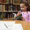 Manchester: Jessie Miller reads a book at the Manchester Public Library on Thursday afternoon before studying for a spelling test. Photo by Kate Glass/Gloucester Daily Times