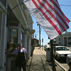 Patty Philbrick of Two Sisters Coffee Shop in Gloucester, watches as her Flag of Honor blows in the wind outside the restaurant yesterday morning. The flag contains the names of those killed in the terrorist attacks of September 11th and Philbrick put it up after hearing the news that Osama bin Laden had been killed. Photo by Kate Glass/Gloucester Daily Times