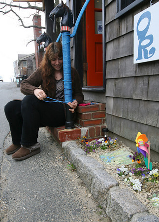 Rockport: Angela Cook wraps blue rope around the bannister leading to her gallery, Oasis Rockport, on Bearskin Neck yesterday. Cook, who makes jewelery in addition to her photography work, is planning to open for the season this weekend. Photo by Kate Glass/Gloucester Daily Times