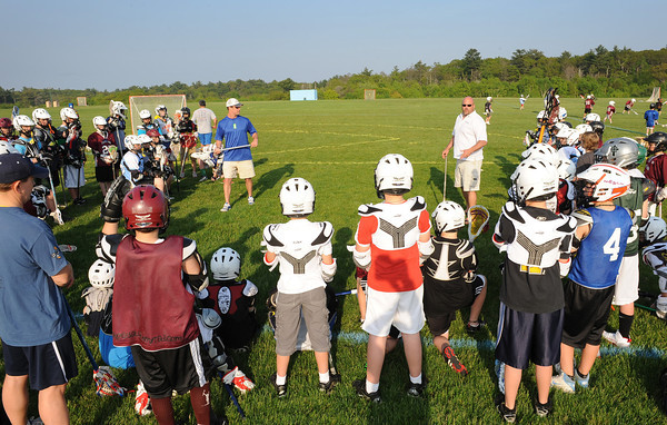 Gloucester:  Former University Virginia All American and Major League Lacrosse, Boston Cannon Face Off Specialist David Jenkins (left) along with Todd Francis (Boston Blazer coach)  talk with a group up U-9  players about handling the ball at  at Free youth Lacrosse Clinic at Magnolia Woods Friday afternoon. Desi Smith/Gloucester Daily Times.