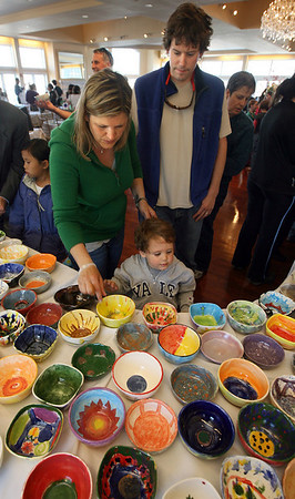 Stefanie and Wes Dukes of Gloucester help their son, Harrison, 3, select a bowl during the Empty Bowl Dinner at Cruiseport yesterday. All proceeds from the event benefit the Open Door. Photo by Kate Glass/Gloucester Daily Times