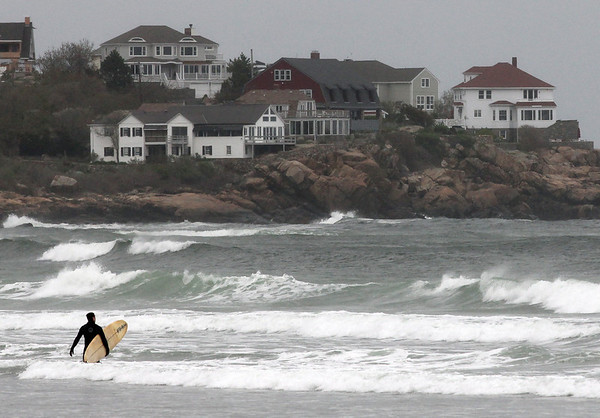A surfer heads into the waves at Good Harbor Beach yesterday. An offshore storm made for choppy surf. Photo by Kate Glass/Gloucester Daily Times