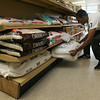 Angel Hernandez pulls a 100 lb. bag of rice from the shelf at Miguel's Grocery Store on Maplewood Ave. Hernandez says the large bags of rice are one of their biggest sellers. Photo by Kate Glass/Gloucester Daily Times