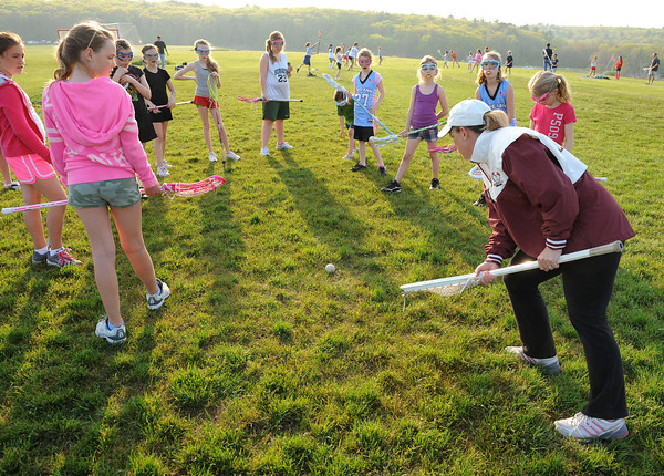 Gloucester:  Coach Meghan MacLaughlin  shows a group of girls the right way pich up the ball and go and how to avoid being checked, at Free youth Lacrosse Clinic at Magnolia Woods Friday afternoon, put on by former University Virginia All American and Major League Lacrosse, Boston Cannon Face Off Specialist David Jenkins along with Todd Francis (Boston Blazer coach).Desi Smith/Gloucester Daily Times