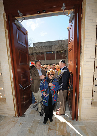 Gloucester: Irma Cohen carries the memora through the doors that survived the 2007 fire into the Temple Ahavat Achim on Middle Street Sunday morning. Desi Smith/Gloucester Daily Times.
