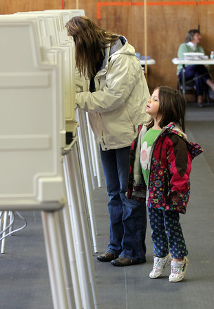 Manchester: Summer Demeo, 3, stands on her tiptoes to get a better view as Patty Brennan fills out her ballot in the Manchester election yesterday. Photo by Kate Glass/Gloucester Daily Times