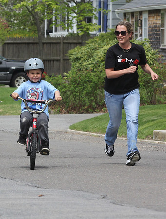 Rockport: Erin Mock runs alongside her son, Kaikoa Birtodaso, 5, as he learns to ride a bike without training wheels yesterday afternoon. Photo by Kate Glass/Gloucester Daily Times
