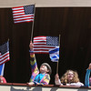 Gloucester: Left to right Judy Bloomfield, Rebecca Dowe 10, August Kahle 10,  and Yishai Howe 7, wave their flags on the balconey of  their new place of worship on Middle Street Sunday morning. Desi Smith/Gloucester Daily Times.