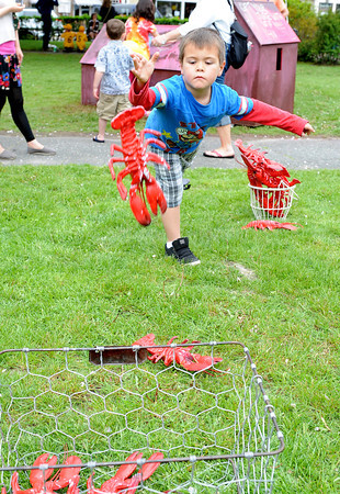 Rockport: Kaikoa Birtodaso 5,of Rockport tosses plastic lobsters into a wire basket at Motif#1 Celebration Day Saturday afternoon. Get three in, get a free tattoo. Desi Smith/Gloucester Daily Times.