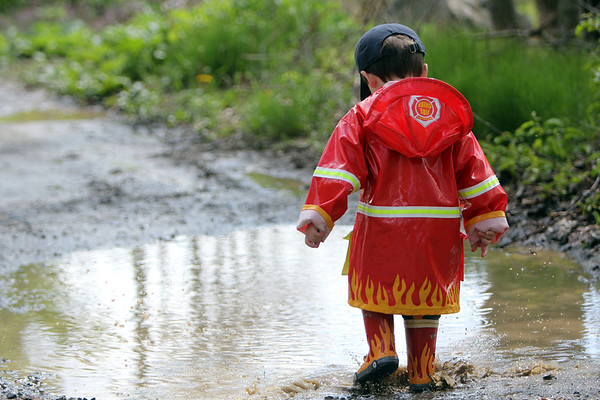 ALLEGRA BOVERMAN/Staff photo. Gloucester Daily Times. Essex: Jackson Bartlett, 2, of Essex, stomps (along with his sister Sydney, 4, not shown) in a puddle while awaiting friends to arrive so they can hunt for frogs in the Cathedral Pines area on Thursday afternoon.