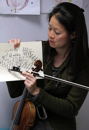 """ALLEGRA BOVERMAN/Staff photo. Gloucester Daily Times. Gloucester: Boston Symphony Orchestra Assistant Concertmaster and violinist Elita Kang came to visit East Gloucester Elementary School on Tuesday and talk about what it's like to be a professional violinist at the BSO, discuss violin craftsmanship, and music in general. She is showing the students where in the orchestra she tends to sit. She will be appearing this weekend as a guest performer with the Cape Ann Symphony for their Mother's Night Out Concert on Sat. May 12 at 8 p.m., and at an open rehearsal on Fri., May 11 at 7:30 p.m. The Cape Ann Symphony concerts are held at the Fuller Auditorium located at Blackburn Circle, Route 128, Gloucester, MA. Fuller Auditorium is handicapped accessible. Ticket prices are $35 for adults, $30 for senior citizens, $20 for Young Adults and Free for children age 12 and under. For tickets and information, call 978-281-0543 or visit  <a href=""""http://www.capeannsymphony.org"""">http://www.capeannsymphony.org</a>"""