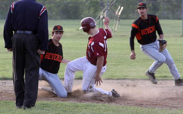 ALLEGRA BOVERMAN/Staff photo. Gloucester Daily Times. Gloucester: Gloucester High School's Logan Horne, center is safe on second base during their game against Beverly on Friday evening. Brandon Sungee of Beverly is on the base.