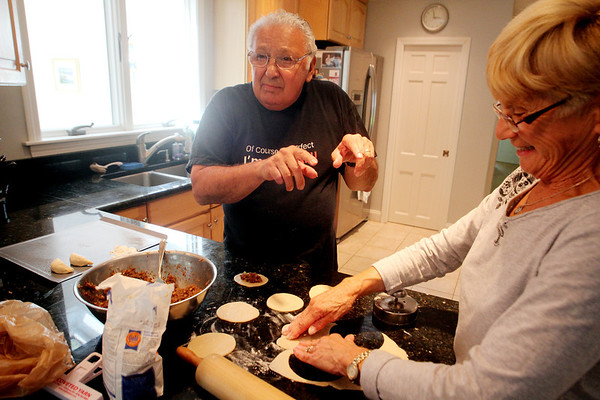 ALLEGRA BOVERMAN/Staff photo. Gloucester Daily Times.  Gloucester: Sam Lucido and his friend Agnes Burnham, both of Gloucester, prepare cuchidata cookies that will be available at the St. Ann's Church Strawberry Festival on June 2. They are joking, as they long have, about whose recipes are better.