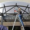 ALLEGRA BOVERMAN/Staff photo. Gloucester Daily Times. Gloucester: Brian Holohan, top, and Keith Linares, of Sign-A-Rama, install the new sign for the new animal shelter.