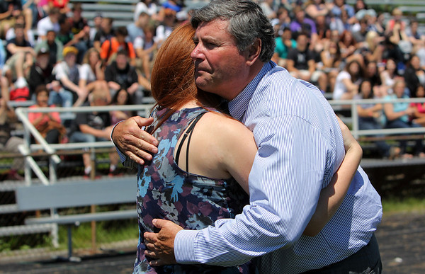 ALLEGRA BOVERMAN/Staff photo. Gloucester Daily Times. Gloucester: Retiring Gloucester High School Principal William Goodwin, right, hugs student council president and senior Eleanor Keller on Thursday afternoon during a surprise tribute to him by the entire school population held at Newell Stadium.