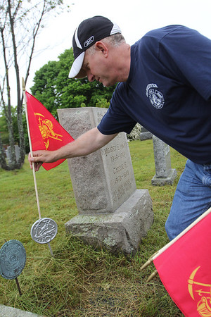 ALLEGRA BOVERMAN/Staff photo. Gloucester Daily Times. Gloucester: Gloucester Firefighter Tony Trupiano places a new flag at the gravesite of Guy Wagner, a city firefighter, at the Cherry Hill Cemetery on Tuesday morning. Flags were placed at gravesites throughout the city's cemeteries on Tuesday in preparation for both Memorial Day, because many firefighters also were veterans, but also for the upcmoing Firefighters Memorial Service to be held at 8:45 a.m. on Sunday, June 10. A parade will step off from the Department of Public Works on Poplar Street and make its way to Cherry Hill Cemetery to the Firefighters Memorial. If it rains, the ceremony will be held at the fire department's headquarters.