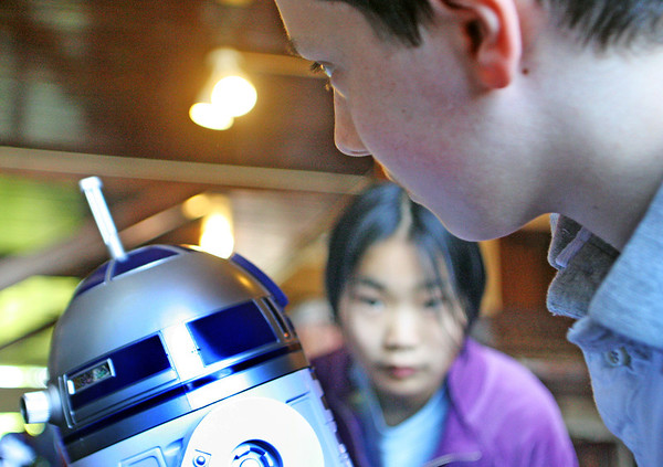 """Jesse Poole/Gloucester Daily Times May 12, 2012 GLOUCESTER— Kevin Nolan, 13, says """"Do you remember Darth Vader?"""" to a miniature version of Star Wars' R2D2 in anticipation for an audible reply as Lucy Garberg, 10, watches. This was part of a robotics display at City Hall for the city-wide art festival and show-case on Saturday."""