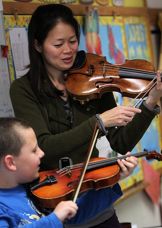 """ALLEGRA BOVERMAN/Staff photo. Gloucester Daily Times. Gloucester: Boston Symphony Orchestra Assistant Concertmaster and violinist Elita Kang came to visit East Gloucester Elementary School on Tuesday and talk about what it's like to be a professional violinist at the BSO, discuss violin craftsmanship, and music in general. She is showing third grader Cameron Dempsey how to play a student violin. She will be appearing this weekend as a guest performer with the Cape Ann Symphony for their Mother's Night Out Concert on Sat. May 12 at 8 p.m., and at an open rehearsal on Fri., May 11 at 7:30 p.m. The Cape Ann Symphony concerts are held at the Fuller Auditorium located at Blackburn Circle, Route 128, Gloucester, MA. Fuller Auditorium is handicapped accessible. Ticket prices are $35 for adults, $30 for senior citizens, $20 for Young Adults and Free for children age 12 and under. For tickets and information, call 978-281-0543 or visit  <a href=""""http://www.capeannsymphony.org"""">http://www.capeannsymphony.org</a>"""