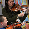 "ALLEGRA BOVERMAN/Staff photo. Gloucester Daily Times. Gloucester: Boston Symphony Orchestra Assistant Concertmaster and violinist Elita Kang came to visit East Gloucester Elementary School on Tuesday and talk about what it's like to be a professional violinist at the BSO, discuss violin craftsmanship, and music in general. She is showing third grader Cameron Dempsey how to play a student violin. She will be appearing this weekend as a guest performer with the Cape Ann Symphony for their Mother's Night Out Concert on Sat. May 12 at 8 p.m., and at an open rehearsal on Fri., May 11 at 7:30 p.m. The Cape Ann Symphony concerts are held at the Fuller Auditorium located at Blackburn Circle, Route 128, Gloucester, MA. Fuller Auditorium is handicapped accessible. Ticket prices are $35 for adults, $30 for senior citizens, $20 for Young Adults and Free for children age 12 and under. For tickets and information, call 978-281-0543 or visit  <a href=""http://www.capeannsymphony.org"">http://www.capeannsymphony.org</a>"
