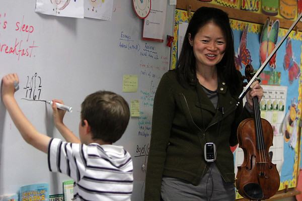 "ALLEGRA BOVERMAN/Staff photo. Gloucester Daily Times. Gloucester: Boston Symphony Orchestra Assistant Concertmaster and violinist Elita Kang came to visit East Gloucester Elementary School on Tuesday and talk about what it's like to be a professional violinist at the BSO, discuss violin craftsmanship, and music in general. Third grader Ryan Bergin tallies up how old her violin is - 245 years old. <br /> She will be appearing this weekend as a guest performer with the Cape Ann Symphony for their Mother's Night Out Concert on Sat. May 12 at 8 p.m., and at an open rehearsal on Fri., May 11 at 7:30 p.m. The Cape Ann Symphony concerts are held at the Fuller Auditorium located at Blackburn Circle, Route 128, Gloucester, MA. Fuller Auditorium is handicapped accessible. Ticket prices are $35 for adults, $30 for senior citizens, $20 for Young Adults and Free for children age 12 and under. For tickets and information, call 978-281-0543 or visit  <a href=""http://www.capeannsymphony.org"">http://www.capeannsymphony.org</a>"