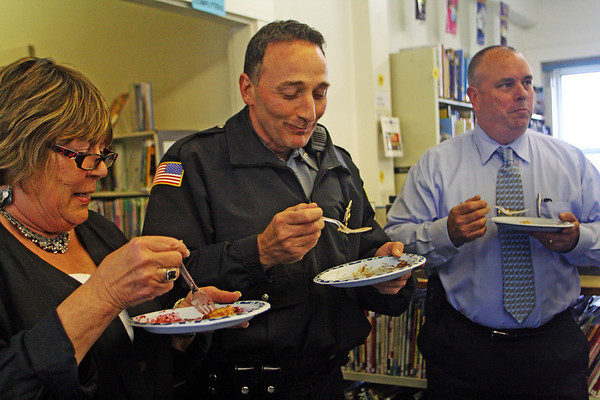 """Each with a different kind of pie in hand, from left, Mary Elinor Dagle, Police Officer Rob Gilardi and Chief of Police Peter Silva visit the T.O.P.H. Burnham Library on Wednesday afternoon for the Annual Pie Fest Fundraiser, which benefits the library. """"Not my first piece of pie, and it won't be my last,"""" joked Gilardi. Jesse Poole/Gloucester Daily Times May 2, 2012"""