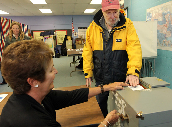 ALLEGRA BOVERMAN/Staff photo. Gloucester Daily Times. Rockport: Liz Pszenny, ballot box attendant, helps Dan Karr to place his ballot inside it during elections at Precinct Three at Rockport Elementary School on Tuesday.