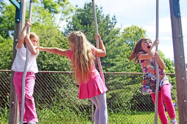 Jesse Poole/Gloucester Daily Times May 23, 2012 MANCHESTER— From left, kindergarteners Mechi O'Neil, Phileine de Widt and Emily Parkins, all girl scouts and members of Daisy's Troop, climb on a playground outside Manchester Memorial Elementary School on Wednesday afternoon.