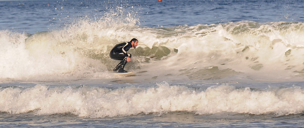 Gloucester: White sea foam surrounds a surfer off Good Harbor Beach in Gloucester Wednesday evening. Jim Vaiknoras /staff photo