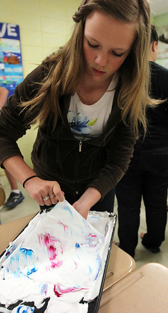 "ALLEGRA BOVERMAN/Staff photo. Gloucester Daily Times. Gloucester: O'Maley Middle School eighth grader Molly White carefully creates a colorful marbled design on paper using shaving cream and washable paint during a workshop on Wednesday. The paper will be incorporated into their ""journey books"" they are making."