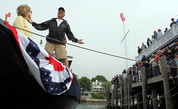 ALLEGRA BOVERMAN/Staff photo. Gloucester Daily Times. ROCKPORT: Capt. Bill Lee of Rockport, standing, asks Neptune to bless his fishing vessel and dename it from Leisy Ana and rename it Ocean Reporter, during a special ceremony in Sandy Bay Harbor at the Sandy Bay Yacht Club on Friday afternoon before dozens of friends and family. Lee's wife Sandy is at left.