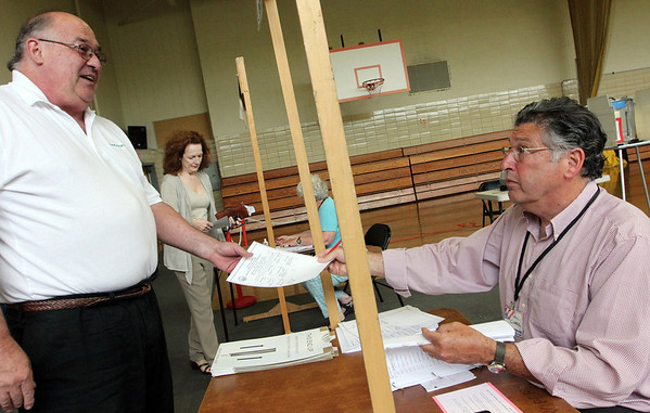 ALLEGRA BOVERMAN/Staff photo. Gloucester Daily Times. Manchester: <br /> Election Official Paul Clark, right, checks in and gives a ballot to Paul Lengieza, left, during Manchester Election Day on Tuesday at Manchester Memorial Elementary School. Also checking in, background center, is Stephanie Morgan, by Election Official Sally Curry.