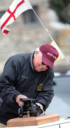 ALLEGRA BOVERMAN/Staff photo. Gloucester Daily Times. ROCKPORT: Bob Smith of Rockport fires one of several small cannons during the ceremony denaming and then renaming the fishing vessel Ocean Reporter on Friday afternoon at Sandy Bay Yacht Club at Sandy Bay Harbor.