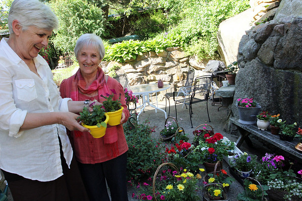 ALLEGRA BOVERMAN/Staff photo. Gloucester Daily Times.  Gloucester: Some of the flower arrangements available for sale, in addition to many perennial plants, during the St. Ann's Strawberry Festival to be held June 2. They are being brought to and also created at the home of Celia Gray, second from left.  Jane Marshall, at left, was helping her out.