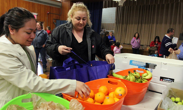 ALLEGRA BOVERMAN/Staff photo. Gloucester Daily Times. Gloucester: From left: Madeline Ortiz and Rosemary Costa select fresh fruits and vegetables at the Mobile Market set up by The Open Door at Veterans Memorial Elementary School on Friday afternoon. The Mobile Market has been in service for seven years in Cape Ann and is in its second year at Veterans Memorial. About 100 families are served by the program, and there is a snack table for kids and adults alike that rotates goodies from week to week. Mobile Market is a free farmers' market, which provides fresh produce and groceries at four neighborhood-based, two school-based, and two senior center-based market sites that include: Riverdale Park, Willowood Gardens, Millbrook Park, Rockport, Pathways for Children, Agawam Village, Ipswich, and Veterans Memorial Elementary School.