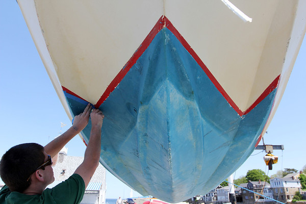 ALLEGRA BOVERMAN/Staff photo. Gloucester Daily Times. Rockport: Andrew Visnick of Rockport prepares a sailboat for scraping and painting at Sandy Bay Yacht Club on Thursday afternoon in preparation for the season.