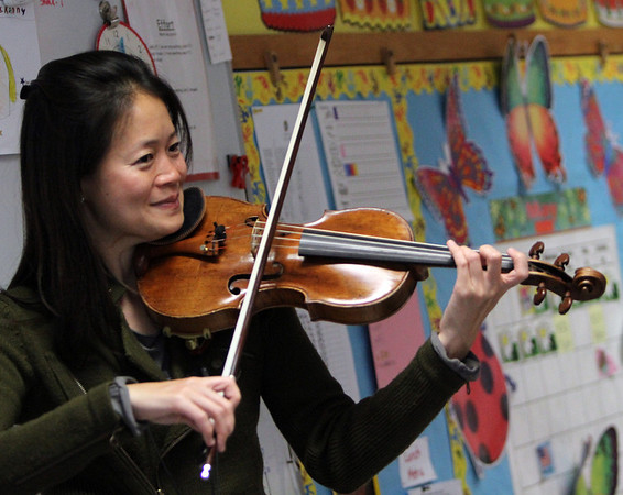 "ALLEGRA BOVERMAN/Staff photo. Gloucester Daily Times. Gloucester: Boston Symphony Orchestra Assistant Concertmaster and violinist Elita Kang came to visit East Gloucester Elementary School on Tuesday and talk about what it's like to be a professional violinist at the BSO, discuss violin craftsmanship, and music in general. She is showing the students where in the orchestra she tends to sit. She will be appearing this weekend as a guest performer with the Cape Ann Symphony for their Mother's Night Out Concert on Sat. May 12 at 8 p.m., and at an open rehearsal on Fri., May 11 at 7:30 p.m. The Cape Ann Symphony concerts are held at the Fuller Auditorium located at Blackburn Circle, Route 128, Gloucester, MA. Fuller Auditorium is handicapped accessible. Ticket prices are $35 for adults, $30 for senior citizens, $20 for Young Adults and Free for children age 12 and under. For tickets and information, call 978-281-0543 or visit  <a href=""http://www.capeannsymphony.org"">http://www.capeannsymphony.org</a>"