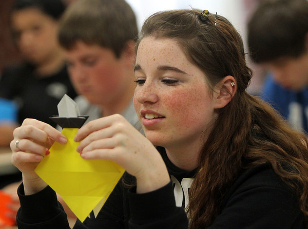 """ALLEGRA BOVERMAN/Staff photo. Gloucester Daily Times. Gloucester: Master Origami Folder Michael LaFosse of Haverhill has been leading three origami workshops with O'Maley Middle School eighth graders. The workshops connected the work they were doing in math, English, science, social studies and art. One group of students made origami dogs, one group made sailboats and the last group made lighthouses, according to their """"academic houses."""" The finished pieces are being hung in the commons, some are already hanging above the stairwell. Charlie Gillon works on her lighthouse on Wednesday morning."""