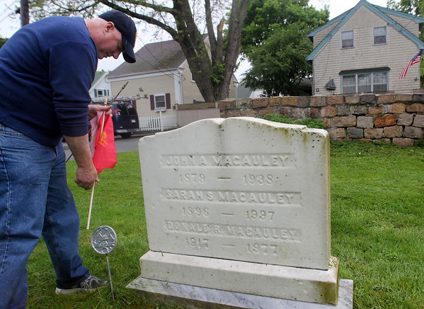 ALLEGRA BOVERMAN/Staff photo. Gloucester Daily Times. Gloucester: Gloucester Firefighter Dan Kennedy places a flag at the gravesite of Maurice T. Dench, Sr., at the Oak Grove Cemetery on Tuesday morning. Flags were placed at gravesites throughout the city's cemeteries on Tuesday in preparation for both Memorial Day,  because many firefighters also were veterans, but also for the upcmoing Firefighters Memorial Service to be held at 8:45 a.m. on Sunday, June 10. A parade will step off from the Department of Public Works on Poplar Street and make its way to Cherry Hill Cemetery to the Firefighters Memorial. If it rains, the ceremony will be held at the fire department's headquarters.